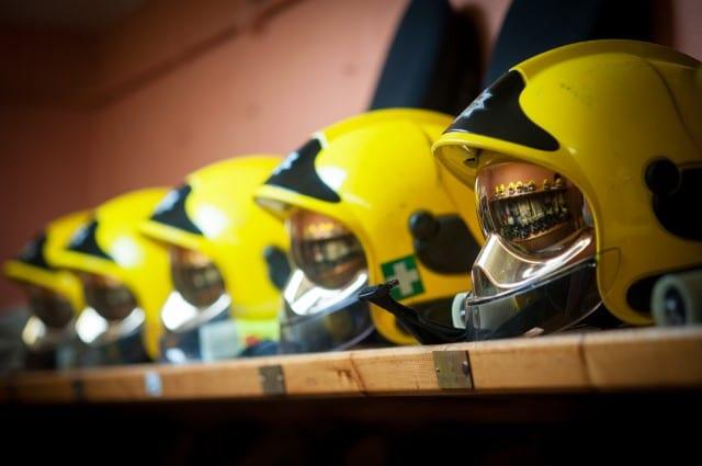 A row of helmets on a shelf